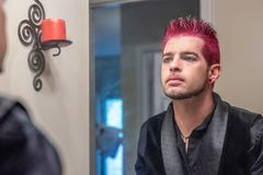 Varón caucásico alternativo con el pelo claveteado rosado que mira en el espejo imagen de archivo libre de regalías