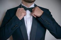 Varón caucásico blanco joven que pone su corbata de lazo en orden, y llevando el traje formal, elegante Fotografía de archivo