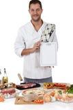 Varón caucásico del cocinero atractivo joven, menú fotografía de archivo