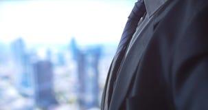 Varón caucásico del hombre de negocios en fondo de la ciudad del lazo de la corbata de la fijación del traje almacen de video