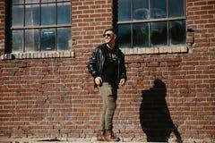 Varón caucásico Guy Walking de la moda moderna atractiva joven, sentándose, sonriendo, y riendo fuera del ladrillo abandonado vie fotos de archivo