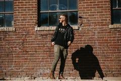 Varón caucásico Guy Walking de la moda moderna atractiva joven, sentándose, sonriendo, y riendo fuera del ladrillo abandonado vie foto de archivo libre de regalías