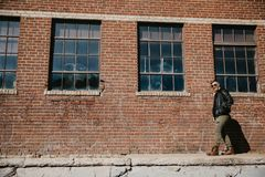Varón caucásico Guy Walking de la moda moderna atractiva joven, sentándose, sonriendo, y riendo fuera del ladrillo abandonado vie imagenes de archivo