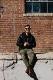 Varón caucásico Guy Walking de la moda moderna atractiva joven, sentándose, sonriendo, y riendo fuera del ladrillo abandonado vie foto de archivo