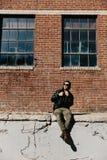 Varón caucásico Guy Walking de la moda moderna atractiva joven, sentándose, sonriendo, y riendo fuera del ladrillo abandonado vie imagen de archivo libre de regalías