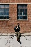 Varón caucásico Guy Walking de la moda moderna atractiva joven, sentándose, sonriendo, y riendo fuera del ladrillo abandonado vie fotografía de archivo libre de regalías