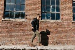 Varón caucásico Guy Walking de la moda moderna atractiva joven, sentándose, sonriendo, y riendo fuera del ladrillo abandonado vie fotos de archivo libres de regalías