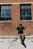 Varón caucásico Guy Walking de la moda moderna atractiva joven, sentándose, sonriendo, y riendo fuera del ladrillo abandonado vie imágenes de archivo libres de regalías