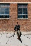 Varón caucásico Guy Walking de la moda moderna atractiva joven, sentándose, sonriendo, y riendo fuera del ladrillo abandonado vie imagen de archivo