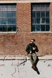 Varón caucásico Guy Walking de la moda moderna atractiva joven, sentándose, sonriendo, y riendo fuera del ladrillo abandonado vie fotografía de archivo
