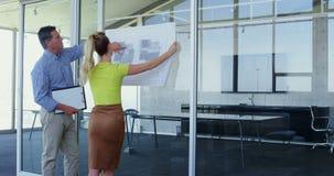 Varón caucásico y arquitectos de sexo femenino que discuten sobre modelo en la oficina 4k metrajes