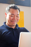 Varón chino en el ordenador portátil Imagenes de archivo