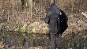 Varón con el comienzo de la mochila que pesca cerca del río metrajes
