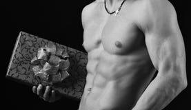 Varón con el torso desnudo aislado en fondo negro Cuerpo de los atletas en cierre para arriba, mano que sostiene la caja de regal fotografía de archivo libre de regalías