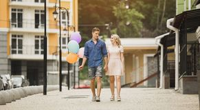 Varón con los globos y hembra que da un paseo abajo de la calle y que habla, fecha romántica Imágenes de archivo libres de regalías