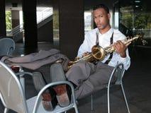 Varón del afroamericano que sostiene su saxofón Foto de archivo libre de regalías