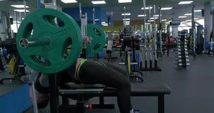 Varón del atleta que hace ejercicios con una barra que se acuesta en el gimnasio Sirva la mentira y empujar la barra de acero en  metrajes