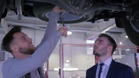 Varón del mecánico con el dueño de la llave y de vehículo bajo parte inferior del coche que habla y que sacude las manos en la ga metrajes