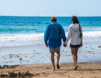 Varón del nacido en el baby boom del jubilado y pares caucásicos femeninos que caminan en la playa hacia el océano que lleva a ca imagenes de archivo