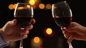 Varón del primer y manos femeninas que tintinean los vidrios con el vino, celebración del fest almacen de metraje de vídeo
