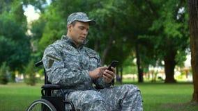 Varón discapacitado en el uso uniforme del smartphone del movimiento en sentido vertical, servicio de empleo metrajes