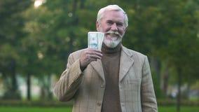 Varón elegante sonriente que lleva a cabo los billetes de dólar, beneficio de negocio financiero del logro almacen de metraje de vídeo