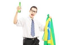 Varón emocionado con la botella de cerveza y la bandera brasileña Fotos de archivo