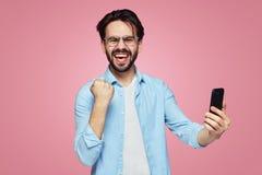 Varón emocionado joven en la camisa azul que sostiene el teléfono móvil y que muestra gesto del ganador con el puño encima de la  foto de archivo