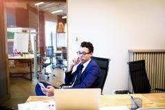Varón en el economista serio de los vidrios que charla en el teléfono móvil que se sienta en la tabla con el ordenador portátil imagen de archivo