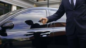 Varón en el traje de negocios que sale del coche costoso y que lo cierra, promoción almacen de metraje de vídeo