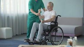 Varón en la silla de ruedas que bombea sus músculos débiles con la ayuda de la enfermera, rehabilitación almacen de metraje de vídeo