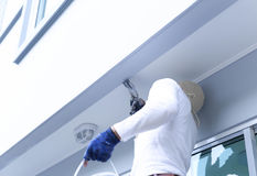 Varón en los guantes que sostienen el edificio de la pintura del cepillo del dolor Imágenes de archivo libres de regalías