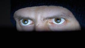 Varón en miradas del sombrero en un monitor del ordenador portátil en la noche metrajes