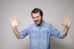 Varón enojado en fondo gris Foto de archivo