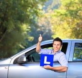 Varón feliz en el coche que lleva a cabo un L muestra Fotos de archivo libres de regalías