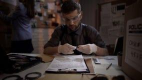 Varón forense del científico que examina la bala de las pruebas de la escena del crimen imágenes de archivo libres de regalías