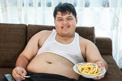 Varón gordo perezoso que se sienta con los alimentos de preparación rápida Imagenes de archivo