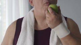 Varón gordo todavía que bebe el agua y que come la manzana verde después de entrenar, dieta almacen de video