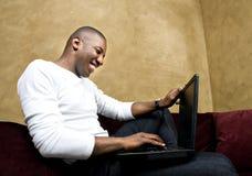 Varón hermoso con la computadora portátil Fotografía de archivo