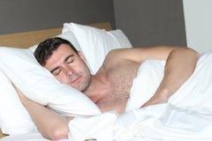 Varón hermoso descamisado que duerme comfortablemente foto de archivo libre de regalías