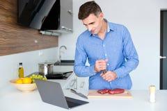 Varón hermoso que mira cocinando la lección en el ordenador portátil y preparándome Imagen de archivo libre de regalías