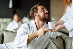 Varón hermoso que recibe su taza de té imagen de archivo