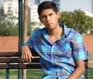 Varón hispánico adolescente que se sienta en banco de parque Fotos de archivo