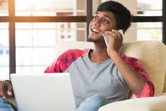 Varón indio adolescente usando el ordenador portátil Foto de archivo libre de regalías