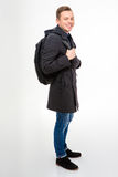 Varón joven alegre positivo en capa y vaqueros con la mochila Fotos de archivo libres de regalías