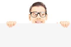 Varón joven asustado con los vidrios que ocultan detrás de un panel Fotos de archivo libres de regalías