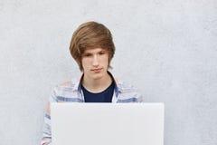 Varón joven con el corte de pelo de moda que se sienta delante del ordenador portátil abierto que lee el libro electrónico con la Foto de archivo