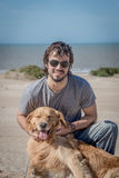 Varón joven con la raza feliz del golden retriever del perro en la playa Fotografía de archivo
