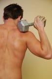 Varón joven con pesa de gimnasia Imagen de archivo