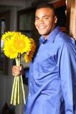 Varón joven del afroamericano con los girasoles Foto de archivo libre de regalías